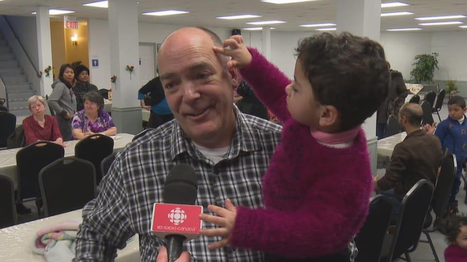Sébastien Groleau porte un enfant dans ses bras en entrevue.