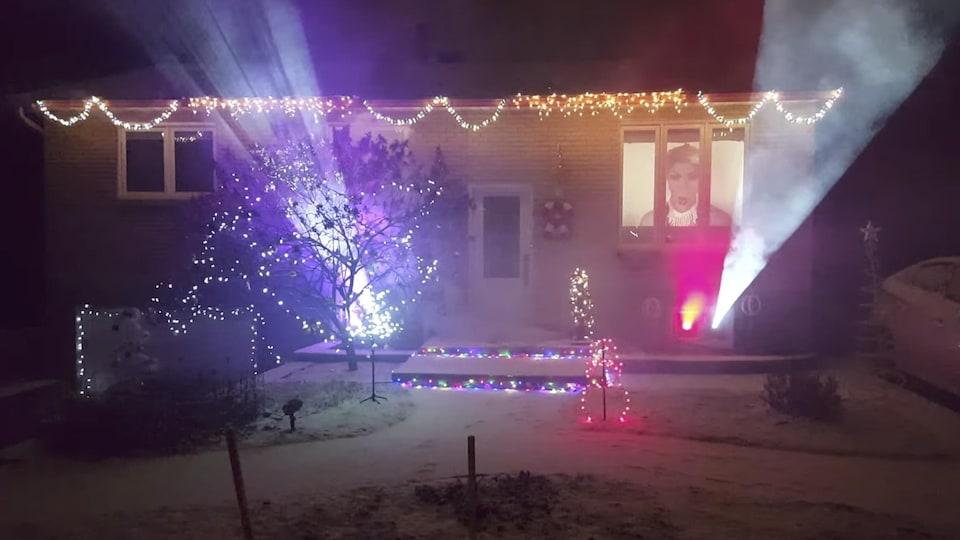 Des faisceaux de lumière sont projetés depuis l'intérieur d'une maison décorée pour les Fêtes.