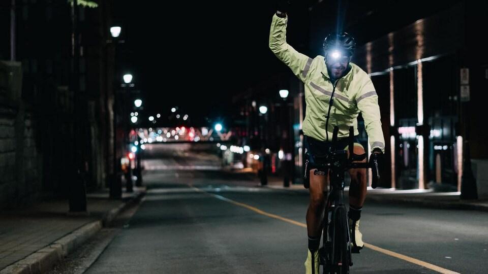 Un cycliste dans une rue déserte, la nuit, poing levé dans une allure triomphale.