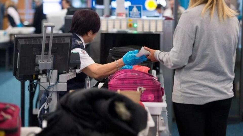 Des agents de la sécurité dans les aéroports fouillent les bagages à mains des passgers.