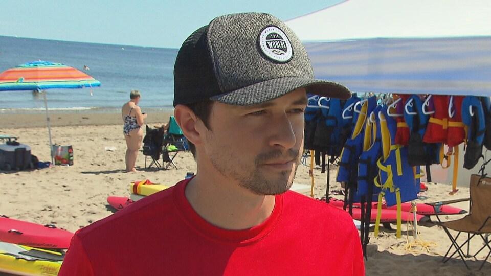 Un homme coiffé d'une casquette se tient sur une plage, près d'un assortiment de gilets de sauvetage.