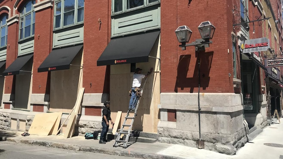 Des ouvriers couvrent les fenêtres d'une boutique La Source à l'aide de panneaux de bois.
