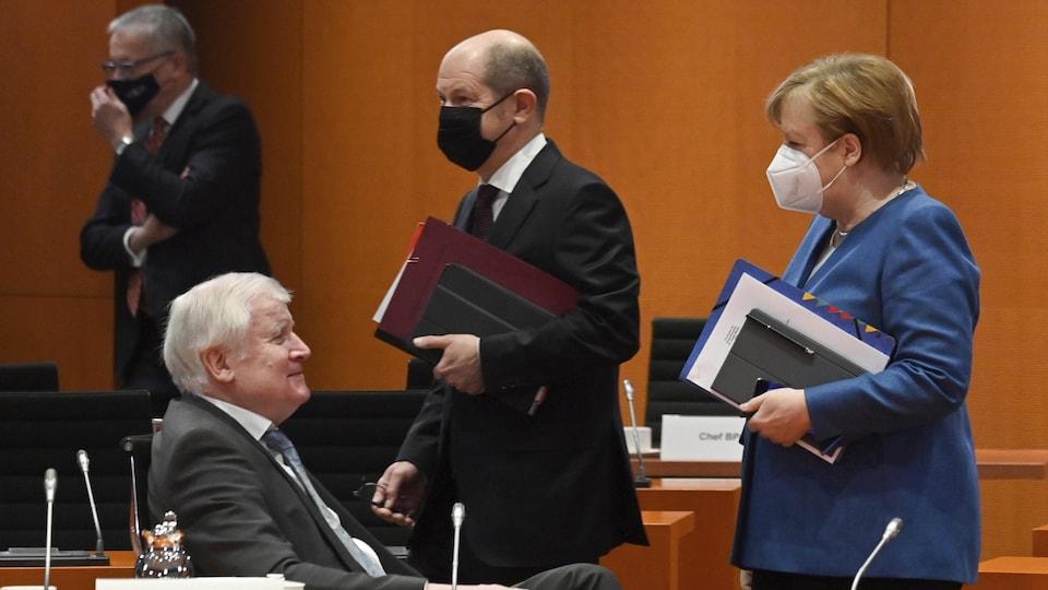 Angela Merkel, debout, discute avec le ministre de l'Intérieur de l'Allemagne Horst Seehofer, qui est assis. Derrière eux, on aperçoit d'autres membres du gouvernement allemand.