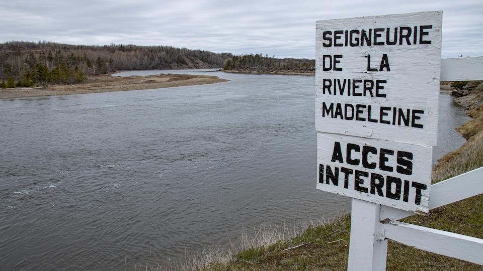 Un panneau inscrit accès interdit sur le bord d'une rivière.