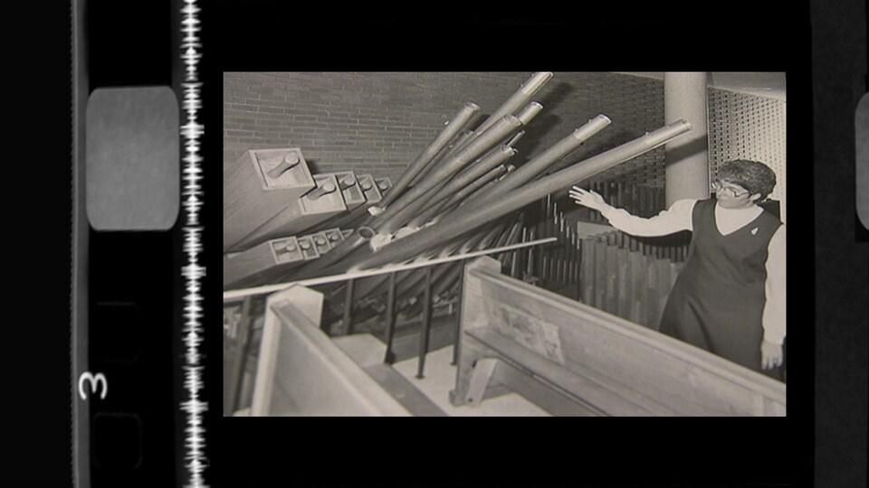 Une religieuse constate les dégâts causés à l'orgue, dont les tubes sont renversés sur les bancs d'église.