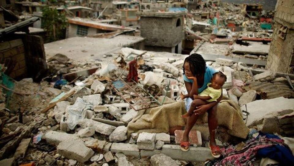 Une femme et son enfant assis dans les ruines.