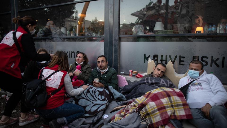 Des secouristes s'occupent de trois hommes et une femme assis par terre, avec des couvertures sur eux.