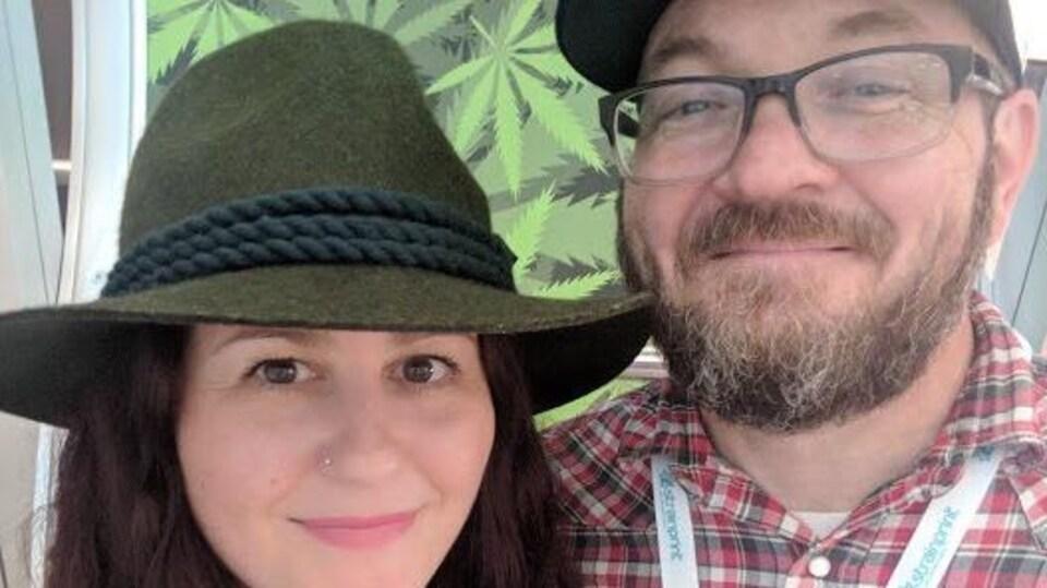 Selina Jane Eckersall et Dean McCall, les fondateurs de Casual Friday Cannabis Ltd. Selina porte un chapeau de couleur kaki, elle a les cheveux longs et bruns mais on ne voit que son visage rapproché, Dean porte une courte barbe poivre et sel, des lunettes à monture noire, il a une casquette et sourit.