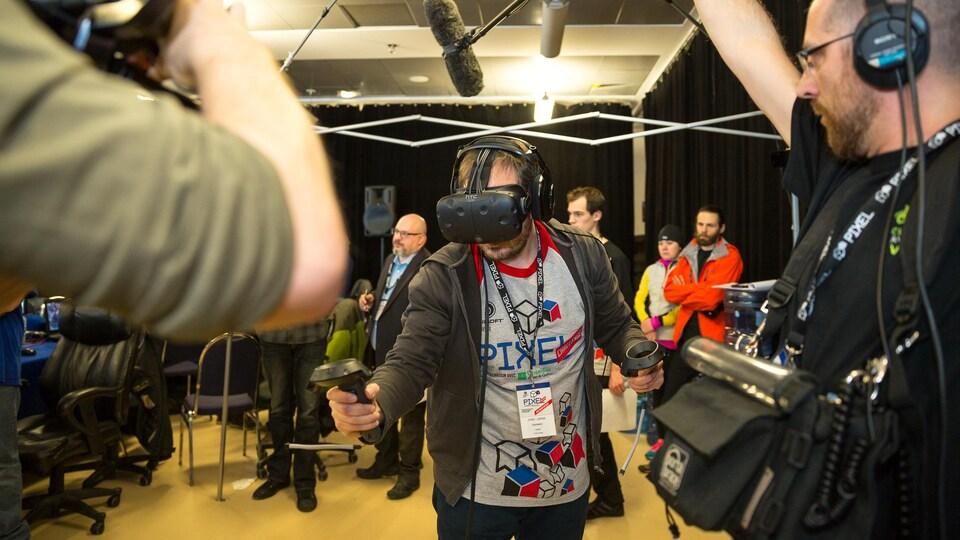 Un participant s'amuse avec un masque de réalité virtuelle pendant qu'un caméraman et un preneur de son l'enregistrent.
