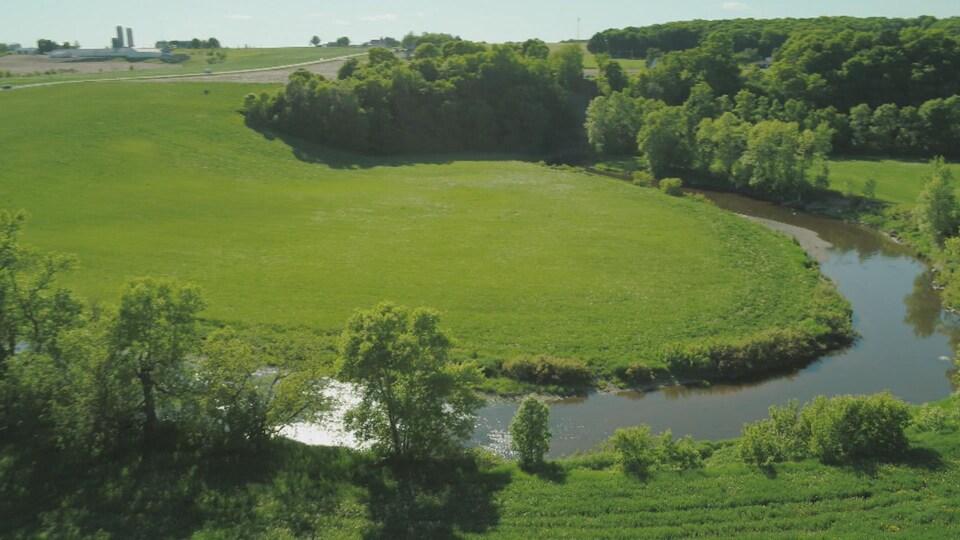 Une terre agricole avec une ferme au loin, et la rivière qui serpente en avant plan.