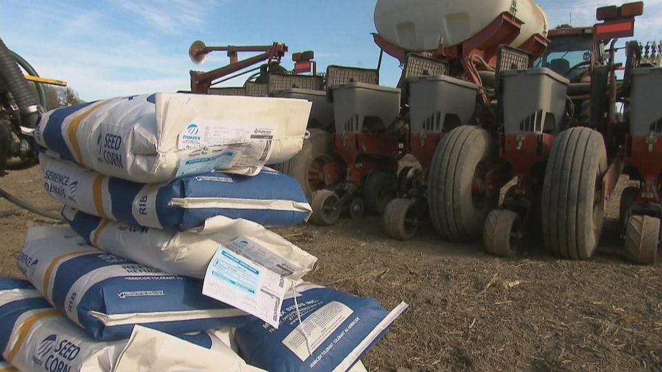 Des sacs de semences enrobées de pesticides derrière un semoir à grains.