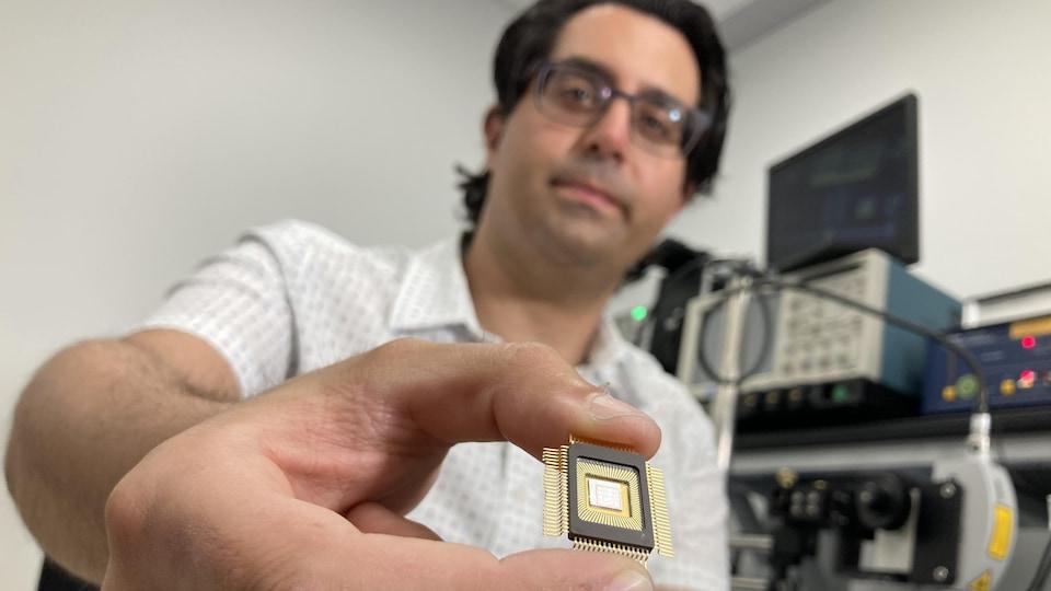 Le professeur en génie électrique de l'École de technologie supérieure Frédéric Nabki tient entre les doigts un semi-conducteur « de recherche ». e