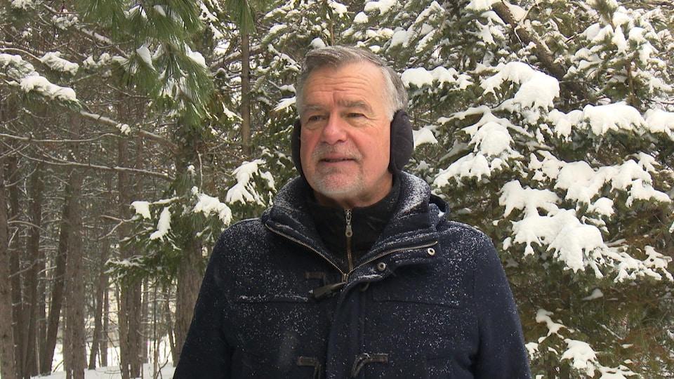 Un homme avec un manteau bleu foncé pose dans une forêt enneigée.