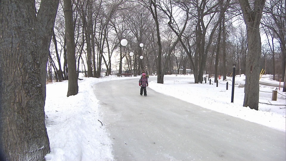 Une fillette marche sur un sentier glacé entouré d'arbres en hiver.