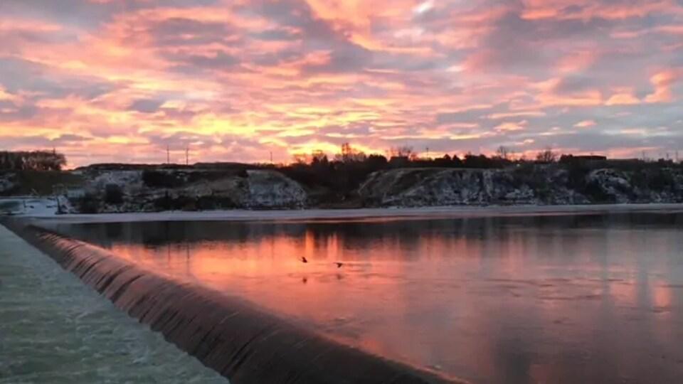 Coucher de soleil sur la rivière Saskatchewan avec quelques collines et des oiseaux qui volent au ras de la rivière.
