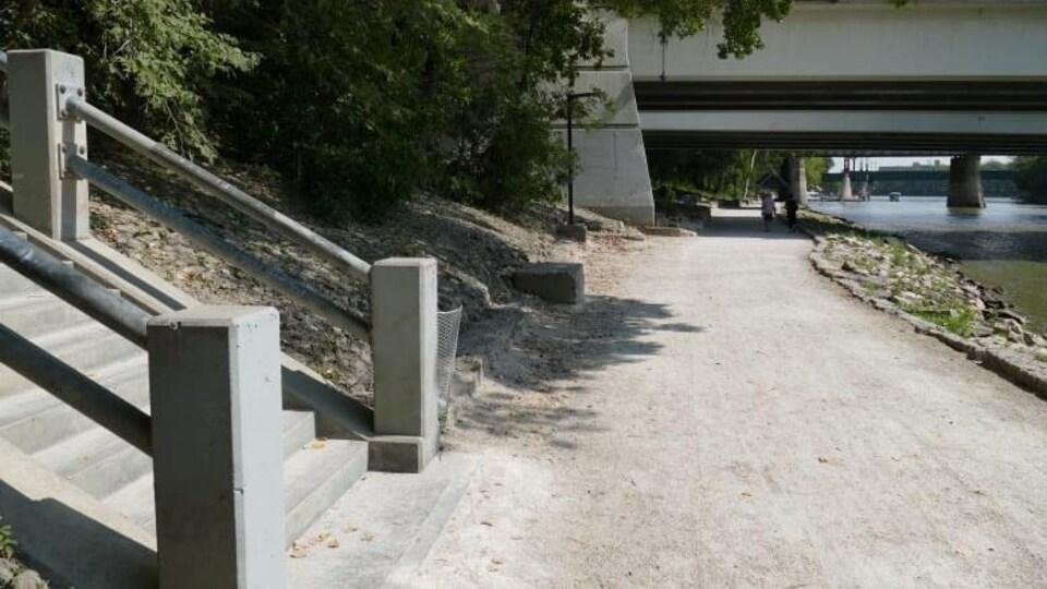 Un sentier longeant une rivière. Au premier plan, on voit à gauche des escaliers. Au fond de la photo, on voit que le sentier passe sous un pont. On voit aussi la silhouette de deux personnes qui y circulent à pied.