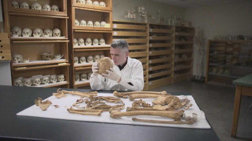 Plan large de Tommy Harding examinant un crâne. Devant lui, sur une table, des ossements humains placés sur un drap. Derrière lui, des crânes sont présentés sur des étagères.