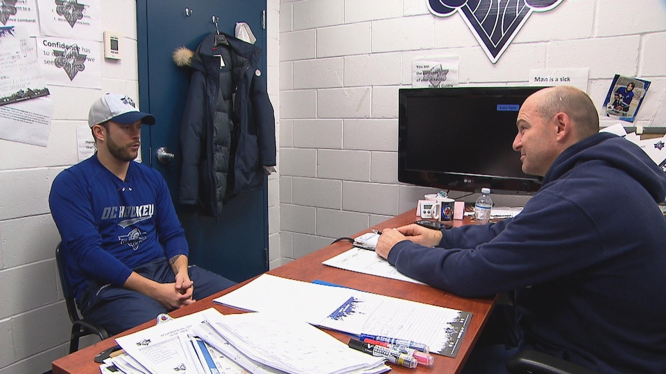 Charles Juneau et Serge Beausoleil sont assis l'un en face de l'autre à un bureau.