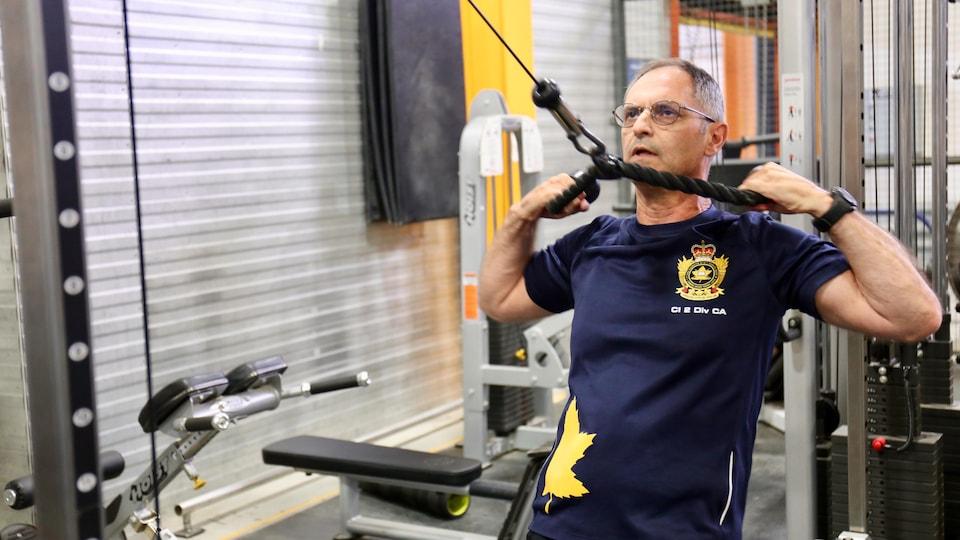Un homme dans la cinquantaine s'entraîne dans un gym. Il tire sur une corde tendue pour soulever des poids et muscler ses bras et ses épaules.