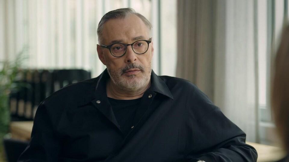 Serge Denoncourt porte une chemise noire et des lunettes noires.