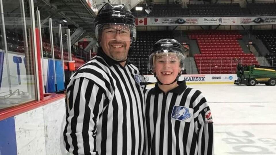Deux arbitres, un père et son fils, sourient à la caméra sur la glace de l'aréna Iamgold de Rouyn-Noranda.