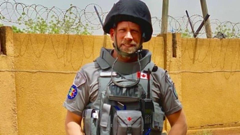 Il sourit en uniforme de combat devant un mur en barbelé.