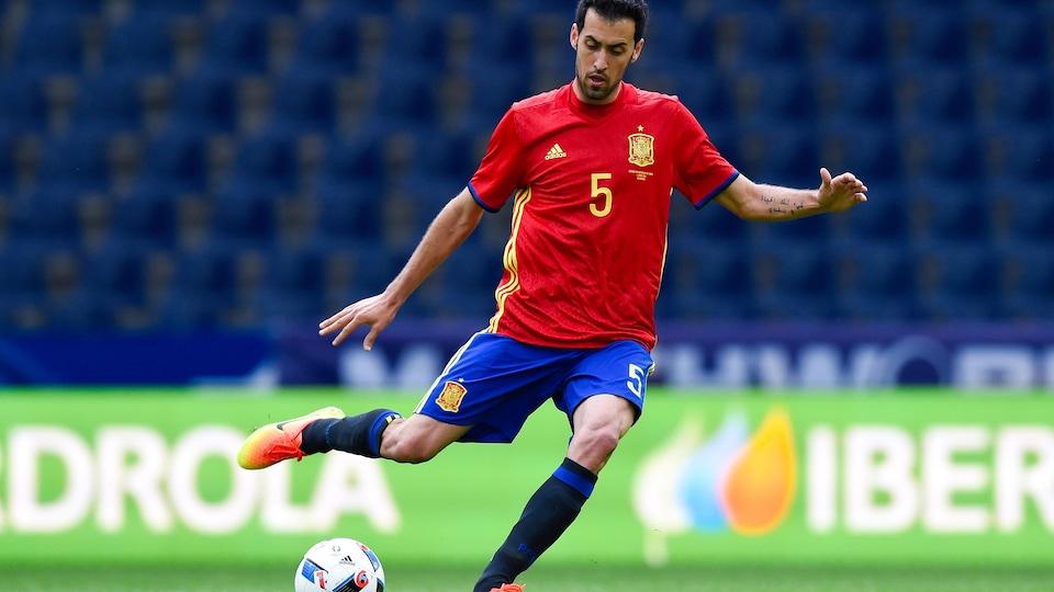 Il botte le ballon alors qu'il porte les couleurs de l'Espagne.