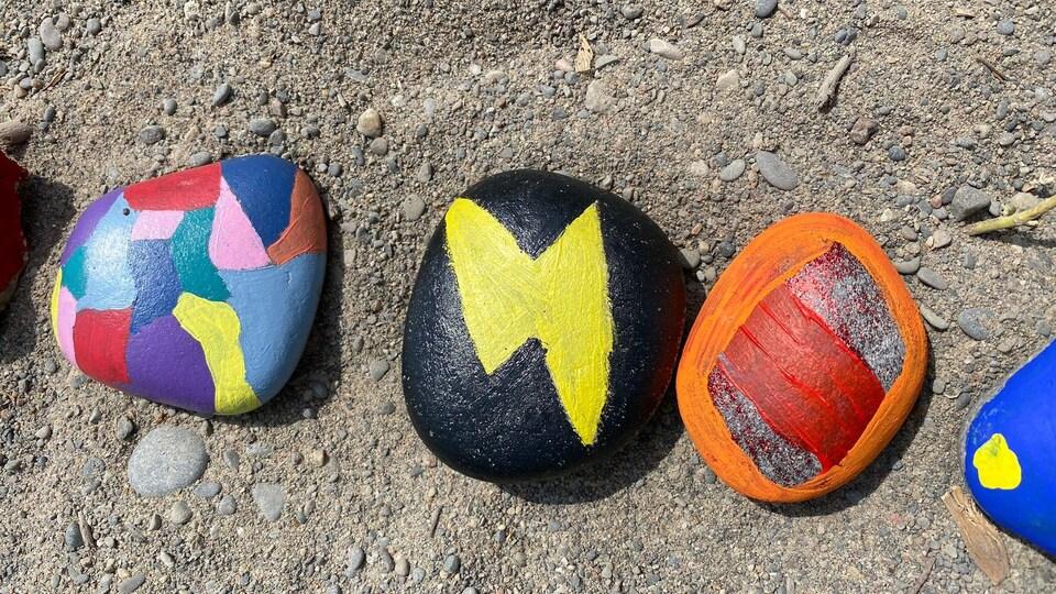 3 roches sur le sable, peintes de différentes couleurs.