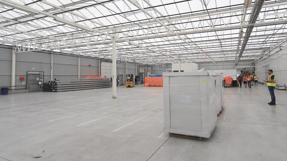 Dans un grand entrepôt vide, on voit 3 boîtes blanches posées au sol.