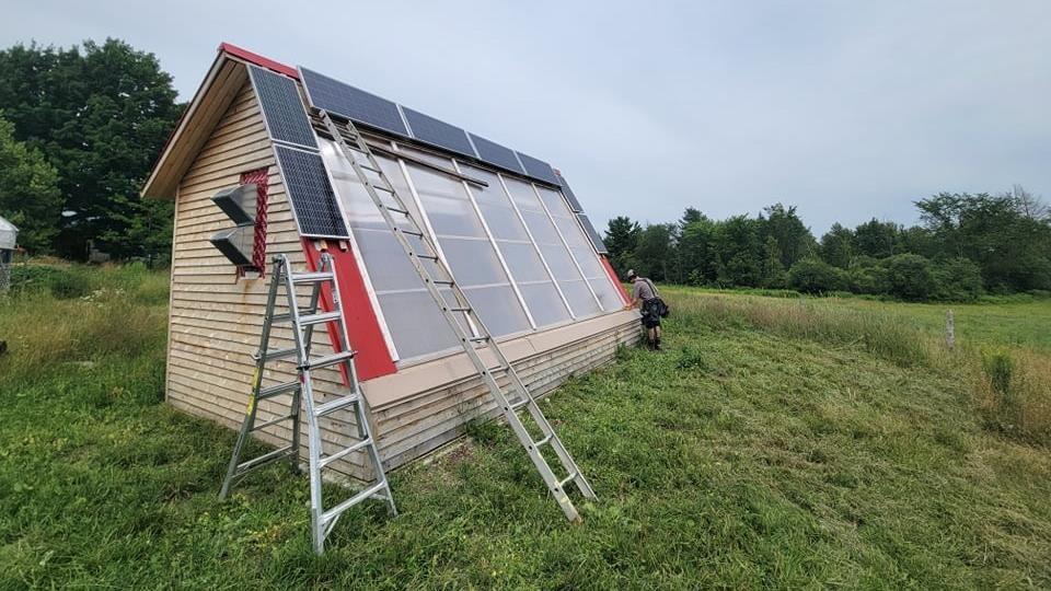 Un petit batiment en bois couvert de panneaux solaires.