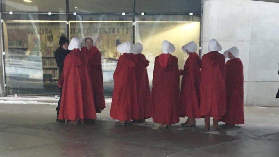 Un groupe d'actrices vêtues de robes rouges et de chapeaux blancs devant un édifice.