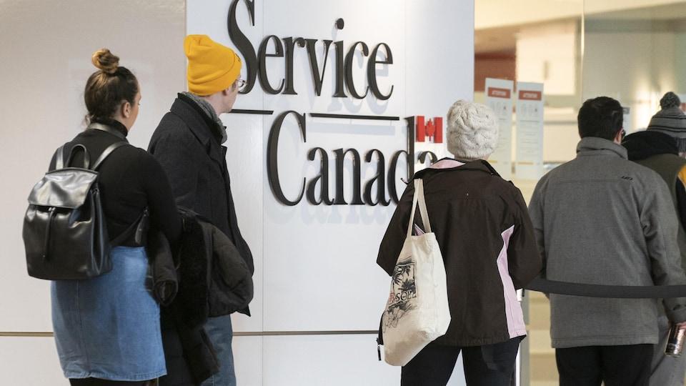 Des gens font la file dans un bureau de Service Canada.