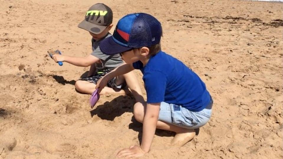 Deux enfants jouent dans sur une plage des Îles-de-la-Madeleine.