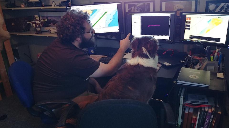 Pierre-Alexandre Lalanne et son chien devant des écrans d'ordinateur où on voit des cartes marines.