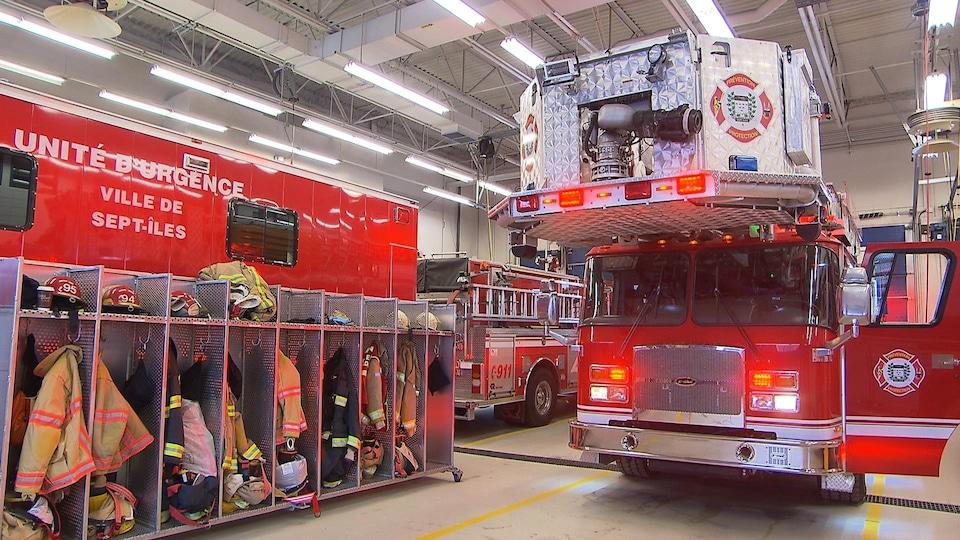 Camions et équipements de pompiers, notamment casiers avec casques et habits, à l'intérieur de la caserne à Sept-Îles.