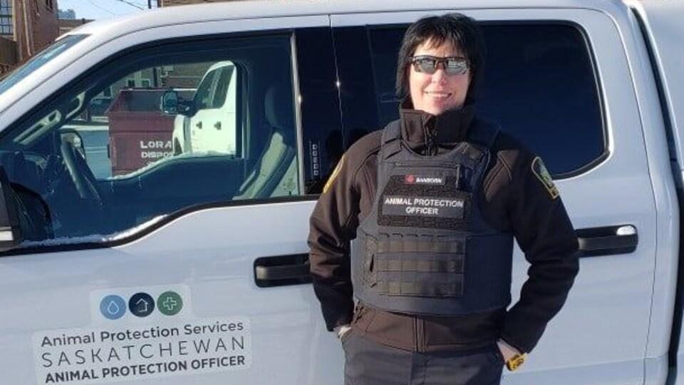 Une agente de la Société des protections des animaux sourit à la caméra alors qu'elle porte son uniforme et des lunettes de soleil. Derrière, une camionnette officielle du Service.