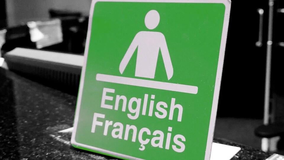 Une affiche où est écrit English Français, avec l'icône d'un homme devant un bureau.