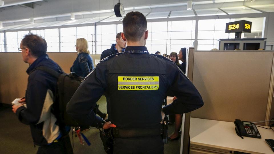 Un douanier de dos à la caméra avec des voyageurs face à lui dans un lieu de transit.