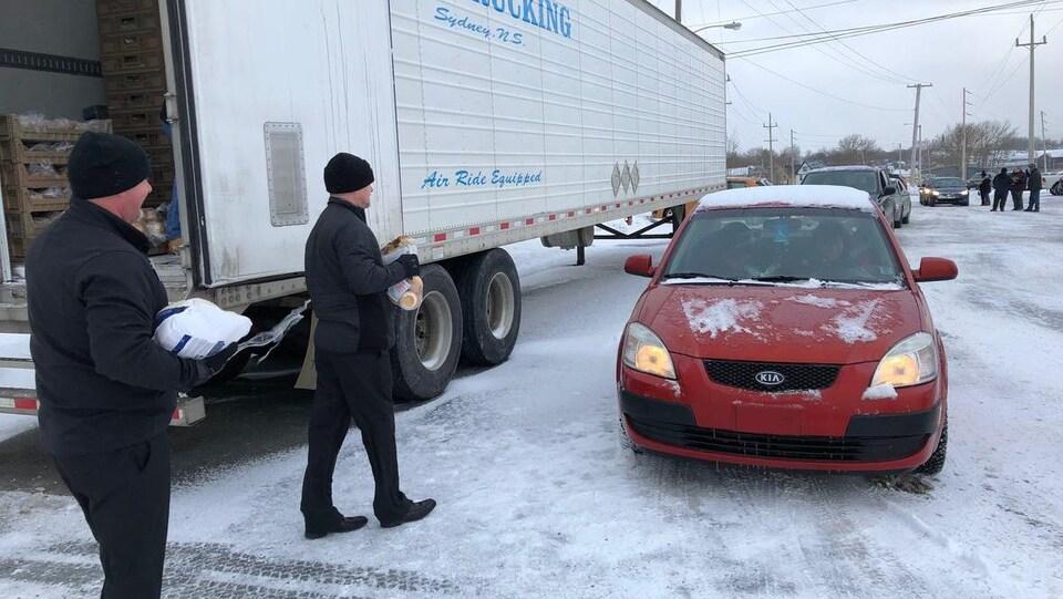 Deux hommes marchent vers une voiture, les bras chargés de victuailles.