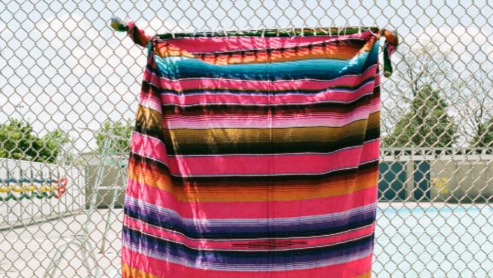 Une serviette rayée multicolore est attachée à une clôture métallique qui entoure une piscine publique.