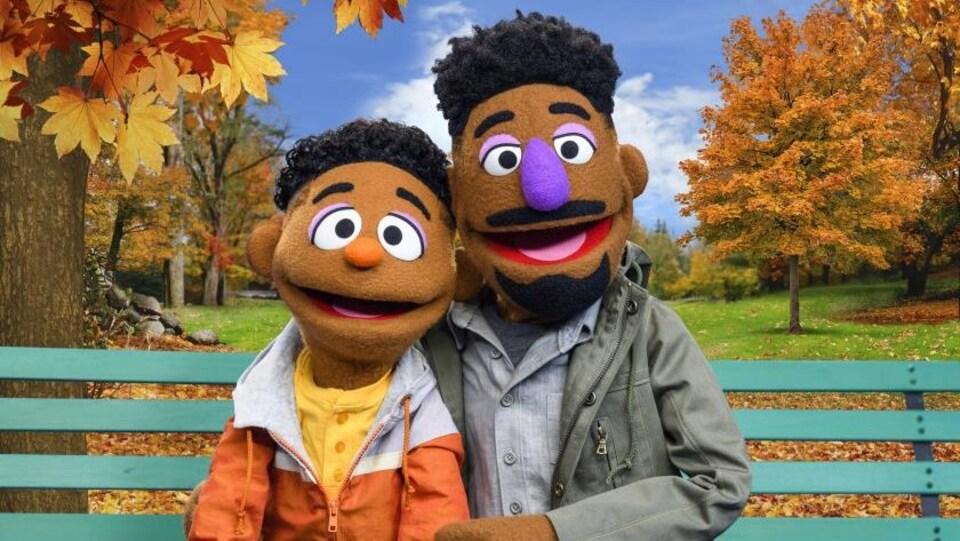Deux marionnettes représentant un père et un fils afroaméricains sont assises sur un banc dans un parc.