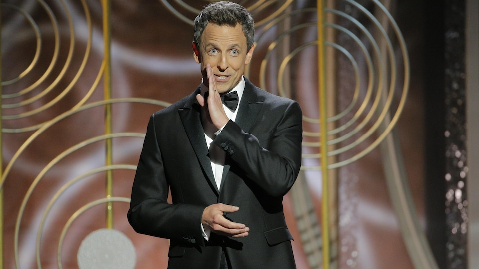 Seth Meyers fait mine de confier un secret au public.