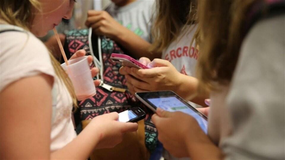 Des adolescentes qui textent sur leur cellulaire.