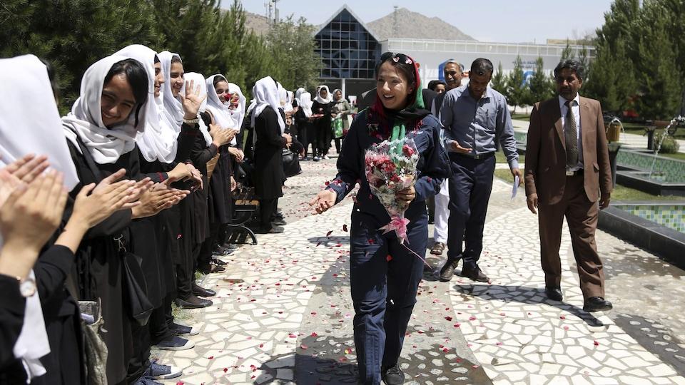Shaesta Waiz marche devant une lignée d'étudiantes afghanes visiblement très heureuses de la rencontrer, devant le bâtiment de la chaîne de télévision Ariana, à Kaboul.