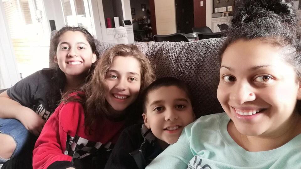 Shaila Wightman sourit sur le canapé avec ses trois enfants.