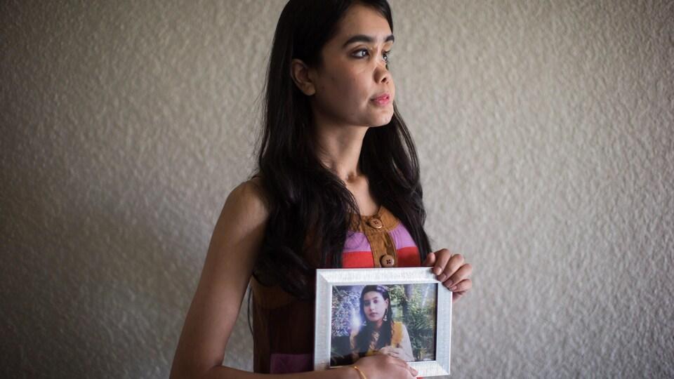Shakila Zareen pose en tenant une photo montrant à quoi ressemblait son visage avant la tragique agression.