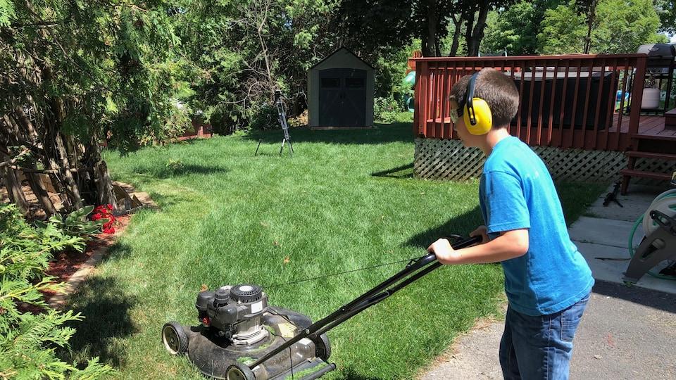 Shan Gauthier pousse une tondeuse à gazon dans une cour de maison.