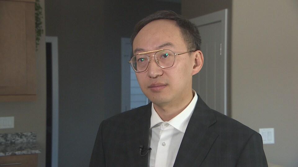 Gros plan sur le visage de Shan Lu qui répond aux questions du journaliste.