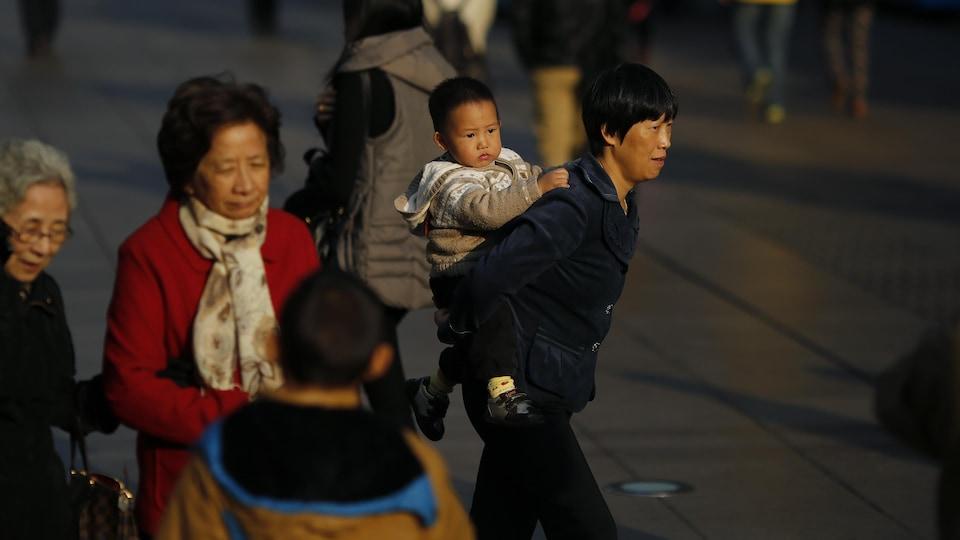 Une femme transporte un bébé sur son dos.