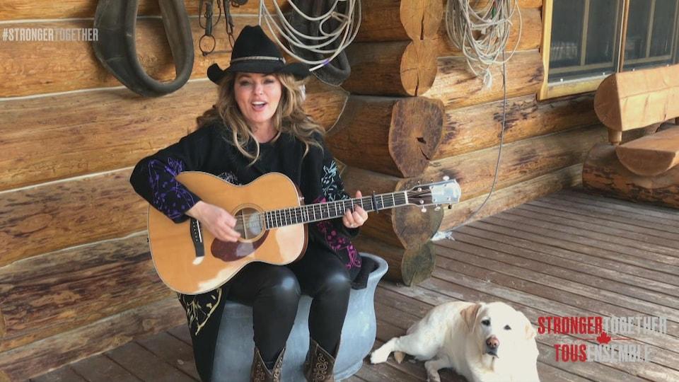 Elle joue de la guitare et chante sur son balcon.